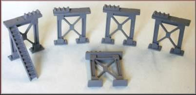 Pack of 5 heavy construction supporting girder 'legs'  cast in whitemetal designed to provide clearance for N gague trains to pass beneath. Supplied with pipe racks and access steps for use as pipe bridge supports.